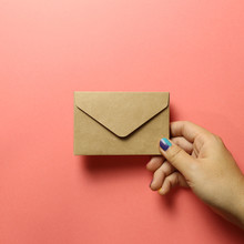 Kraft Brown Paper Envelope With Hand On Pink Background