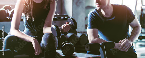 Fotografia Crop image of beautiful sport girl with dumbbell in hand with personal trainer in professional gym, color filter effect selective focus