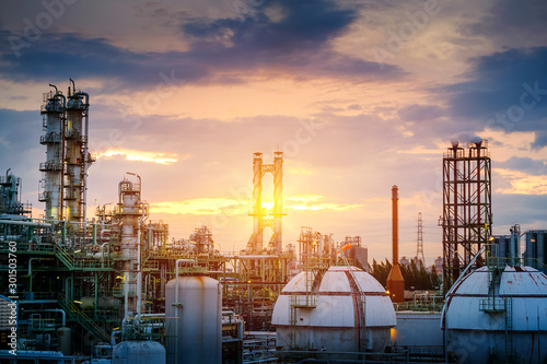 Fototapeta Manufacturing of oil and gas refinery industrial or Petrochemical industry plant on sunset sky background with smoke stacks and gas sphere tanks obraz