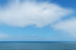Dreamy, blurry sea with cloudy sky.