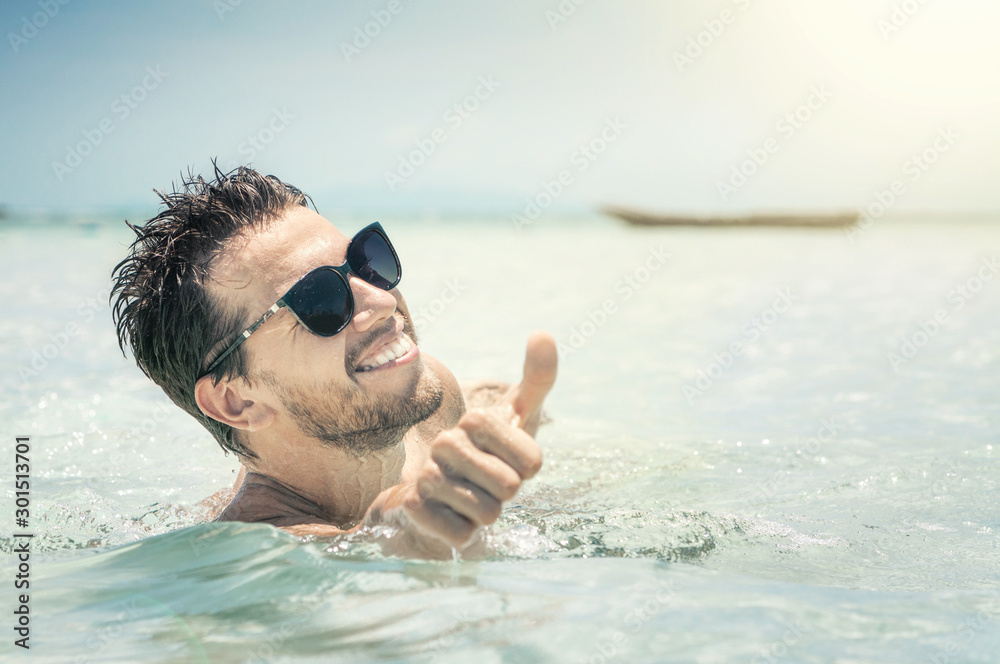 Fototapeta Young handsome man in sunglasses having fun at the sea and showing thumbs up.  Summer vacations concept