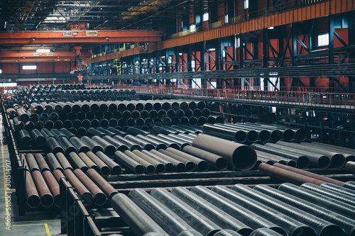 Fototapeta heavy industry concept, construction machinery - long metal pipes inside a large room. Building materials in the hangar obraz