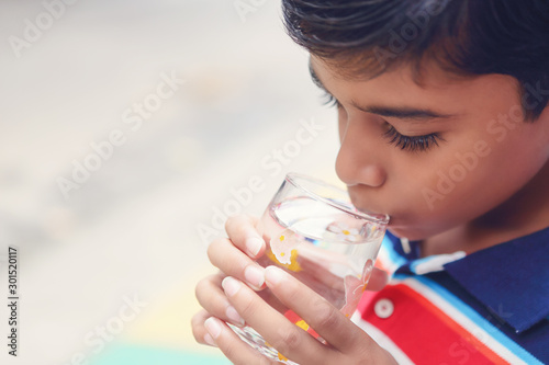 Obraz na plátně Indian little boy showing drinking glass with water