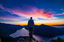 Adventurous Man Watching A Sunset From A Mountaintop.