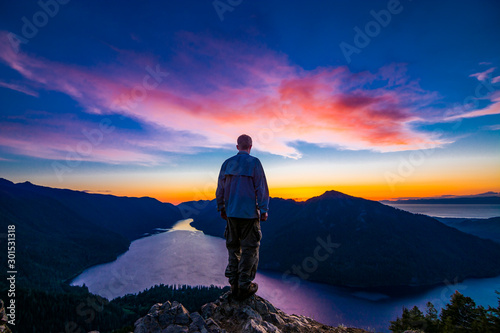Adventurous man watching a sunset from a mountaintop. Canvas Print