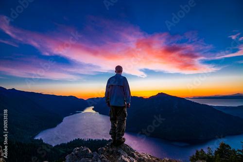 Photo Adventurous man watching a sunset from a mountaintop.