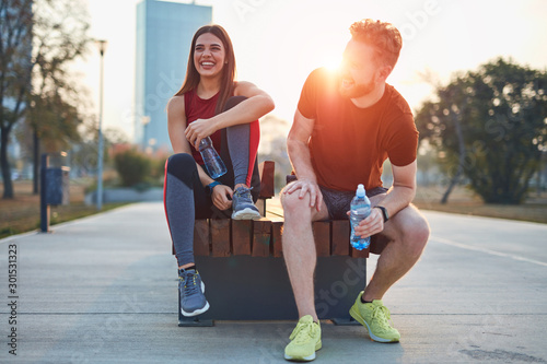 Modern couple making pause in an urban park during jogging / exercise. - 301531323