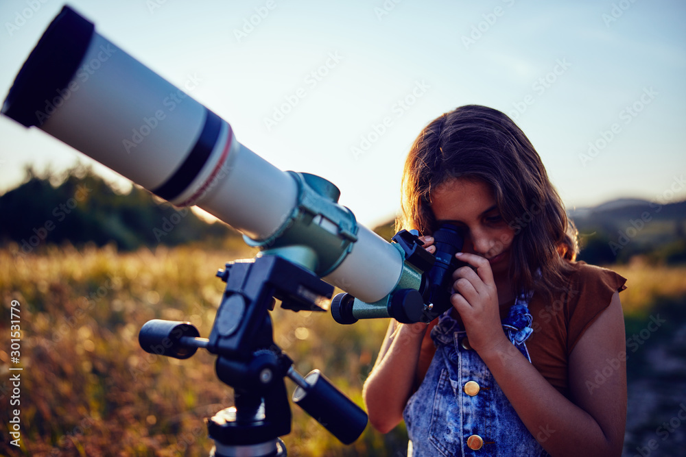 Fototapety, obrazy: Little girl using telescope in nature to explore the universe.