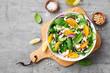Leinwandbild Motiv Fresh spinach salad with oranges, feta (ricotta) cheese, red onion and pine nuts .