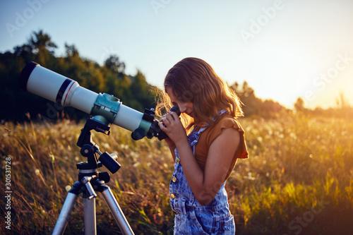 Obraz Little girl using telescope in nature to explore the universe. - fototapety do salonu