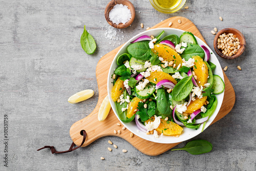 Fotografia Fresh spinach salad with oranges, feta (ricotta) cheese, red onion and pine nuts