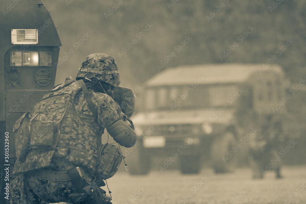 Fototapeta 装甲車の陰で銃を構える自衛官