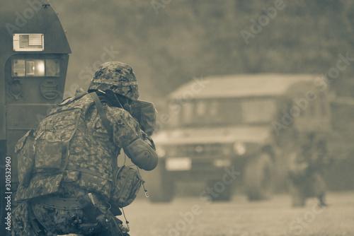 装甲車の陰で銃を構える自衛官 Wallpaper Mural