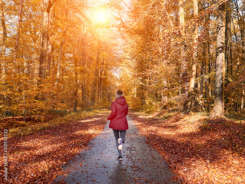 Woman running and training in fall nature Fototapete