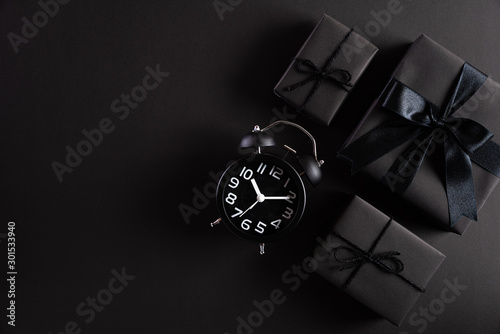 Poster Fleur Top view of Black Friday Sale text with black gift box with Alarm clock on white background. Shopping concept boxing day and black Friday composition.