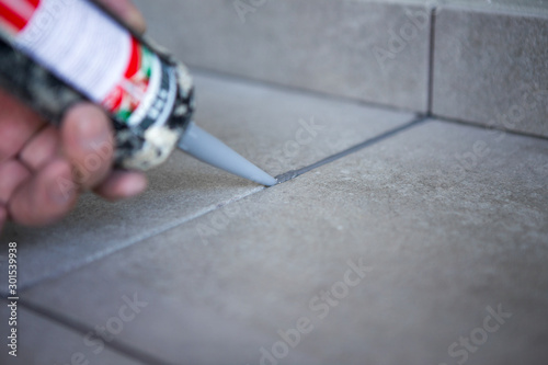 Foto The hand of a construction worker filling the gap between ceramic tiles with sil