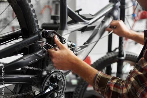 Cropped shot of male mechanic working in bicycle repair shop, repairman fixing bike in a workshop, wearing protective workwear