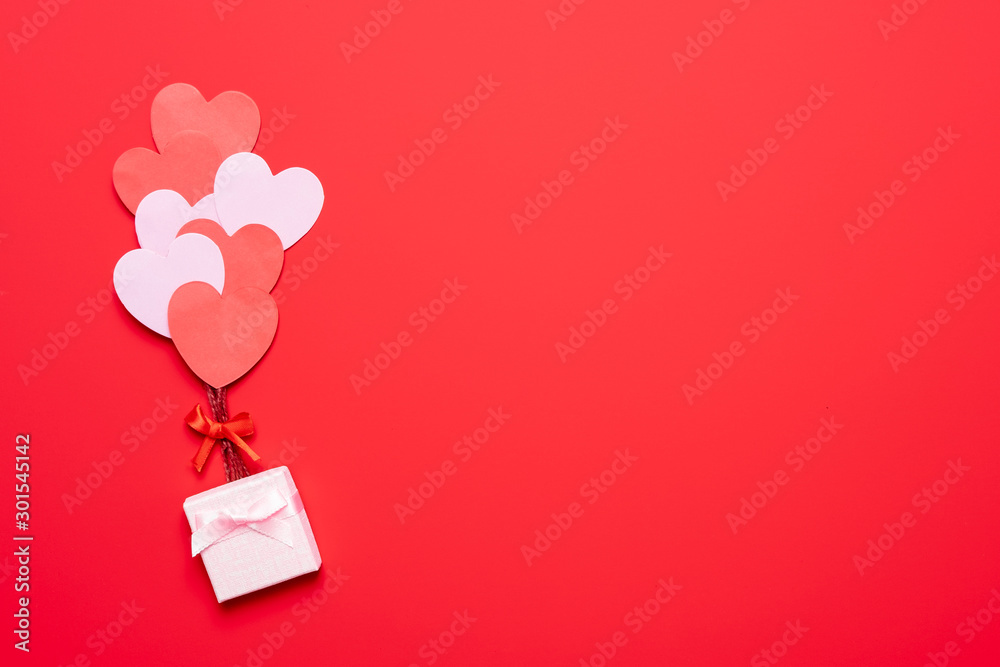 Fototapeta Valentine's day background with red and pink hearts like balloons on pink background, flat lay