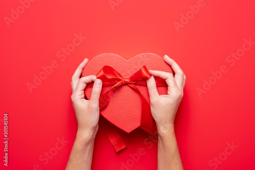 Fototapeta Close up on female hands holding a gift in a pink heart presents for valentine day, birthday, mother's day. Flat lay. Symbol of love. Valentines day background with a gift boxes on concrete board. obraz