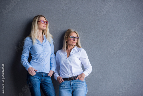 Portrait of two beautiful women of different generations against a gray wall Poster Mural XXL