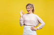 Portrait of satisfied beautiful young woman with blonde hair in casual beige blouse standing, looking at camera showing Ok sign gesture and winking, indoor studio shot isolated on yellow background