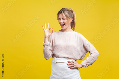 Obraz Portrait of satisfied beautiful young woman with blonde hair in casual beige blouse standing, looking at camera showing Ok sign gesture and winking, indoor studio shot isolated on yellow background - fototapety do salonu