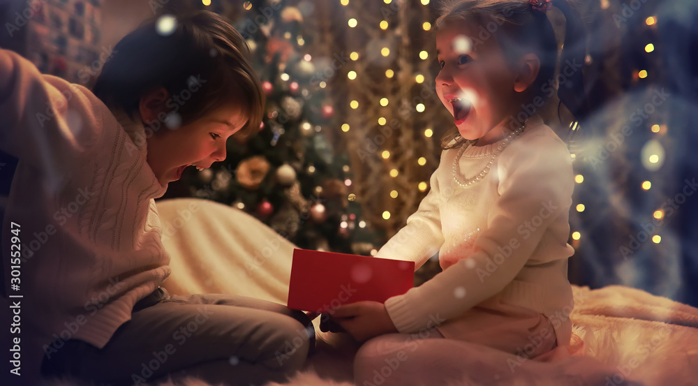 Fototapeta Family on Christmas eve at fireplace. Kids opening Xmas presents. Children under Christmas tree with gift boxes. Decorated living room with traditional fire place. Cozy warm winter evening at home.