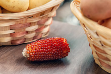 One Ear Of Red Corn Lies Among The Vegetables In The Farmer's Market. Advanced Varieties And Hybrids