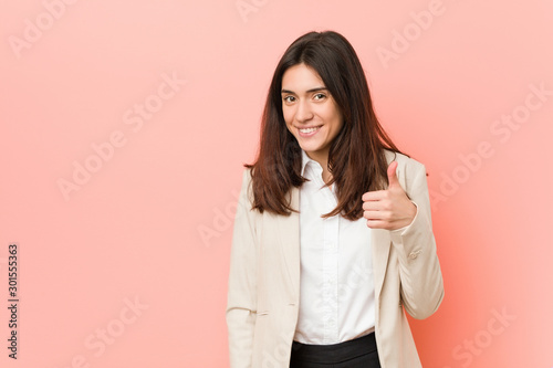 Young brunette business woman against a pink background smiling and raising thumb up