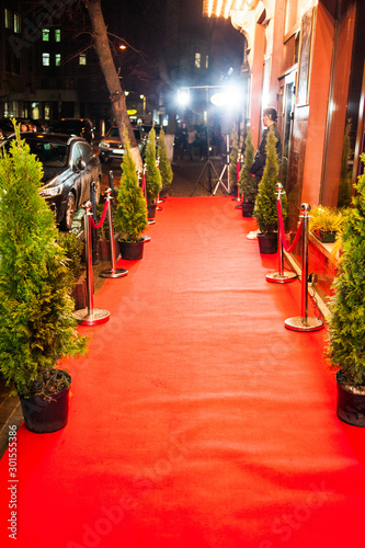 Montage in der Fensternische Rot Long red carpet between rope barriers on entrance.