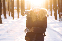 Portrait Of Beautiful Girl In A Blue Jacket And Knitted Hat And Mittens Posing At Sunset In The Winter Forest. Smiling To Camera, Cheerful New Year Mood, True Emotions. Winter Fashion. Christmas.