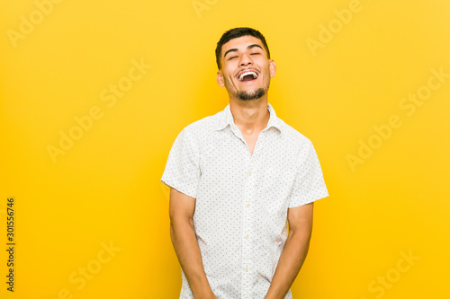 Fotografía  Young hispanic man relaxed and happy laughing, neck stretched showing teeth