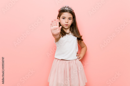 Fotomural  Little girl wearing a princess look standing with outstretched hand showing stop sign, preventing you