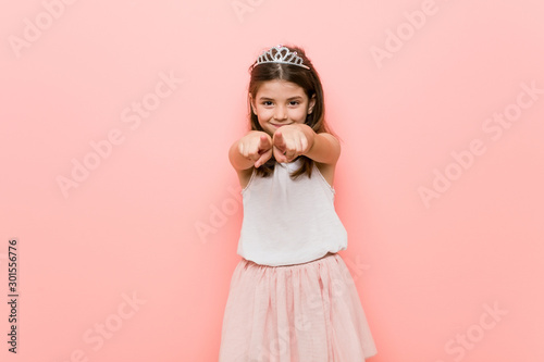 Obraz Little girl wearing a princess look cheerful smiles pointing to front. - fototapety do salonu