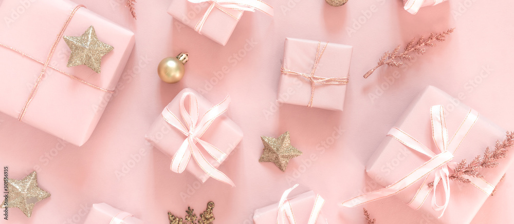 Fototapeta Christmas pink flat lay. Holiday boxes, fir branches on pink background. Christmas winter holiday congratulation invitation birthday wedding.Long banner