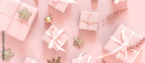 Christmas pink flat lay. Holiday boxes, fir branches on pink background. Christmas winter holiday congratulation invitation birthday wedding.Long banner
