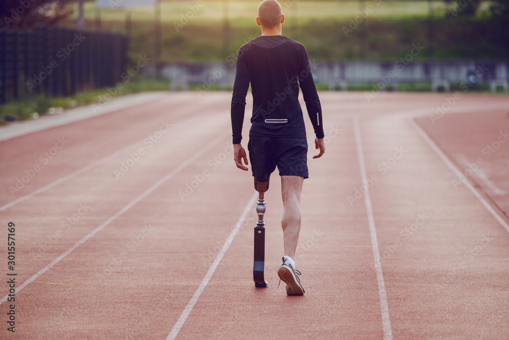 Fototapeta Rear view of handsome caucasian handicapped young man with artificial leg and dressed in shorts and sweatshirt walking on racetrack.