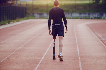 Rear view of handsome caucasian handicapped young man with artificial leg and dressed in shorts and sweatshirt walking on racetrack.