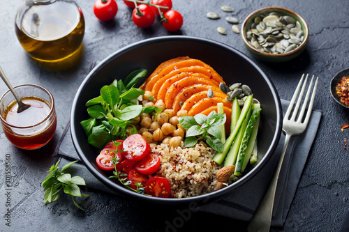 Fototapeta Healthy vegetarian salad. Roasted pumpkin, quinoa, tomatoes, green salad. Buddha bowl. Slate background. Close up. obraz