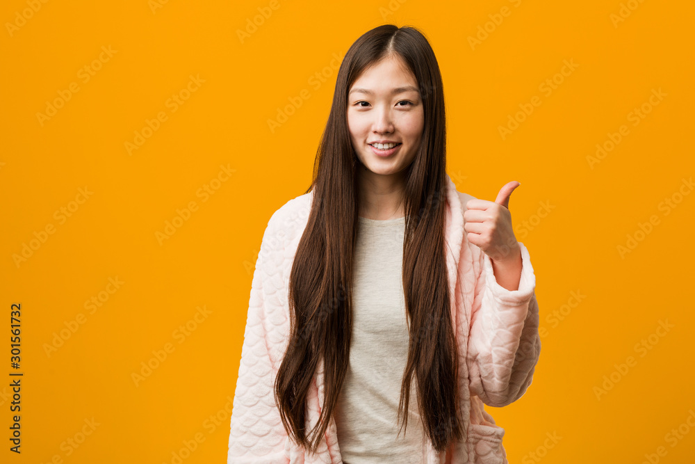 Fototapeta Young chinese woman in pajama smiling and raising thumb up