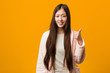 Young chinese woman in pajama smiling and raising thumb up