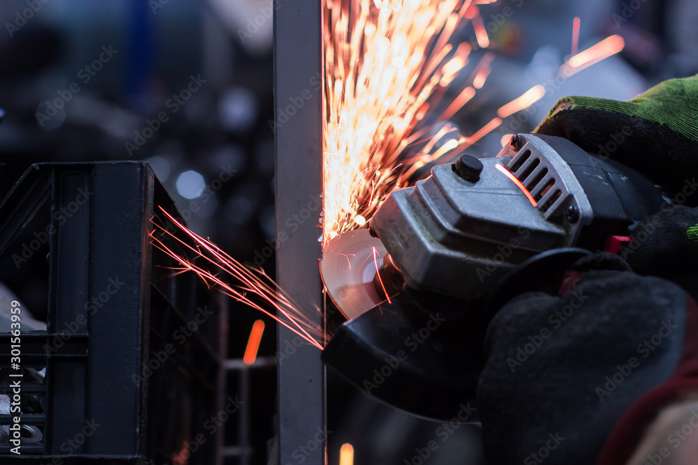 Fototapety, obrazy: Worker cutting metal in the garage