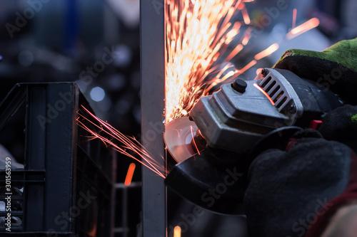 Worker cutting metal in the garage