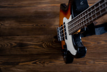 Vintage Bass Guitar In The Upper Right Corner On A Wooden Background. Top View