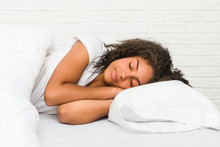 Close Up Of A Young African American Tired Woman Sleeping On The Bed