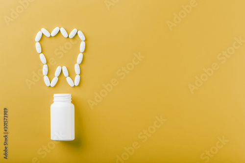 Calcium vitamin in the form of a tooth spilled out of a white jar on a yellow background Wallpaper Mural