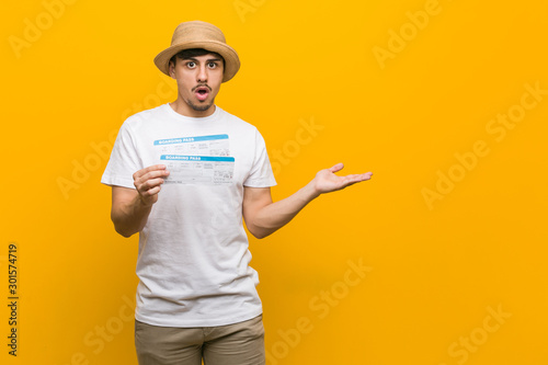 Young hispanic man holding an air tickets impressed holding copy space on palm Slika na platnu