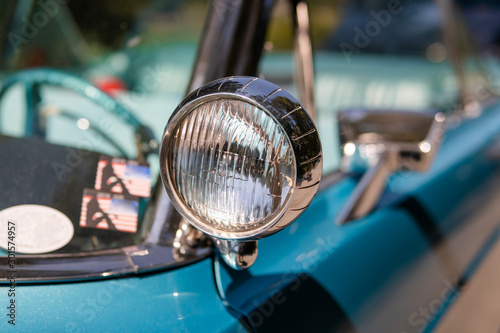 Obraz Color detail on the headlight of a vintage car sky blue color and shiny chrome, selective focus, turquoise - fototapety do salonu