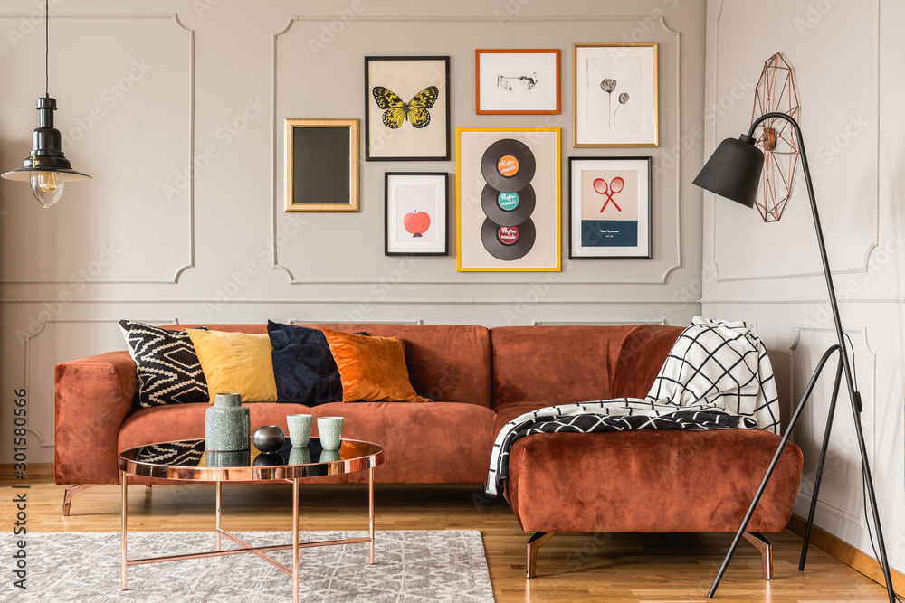 Fototapeta Gallery of trendy posters in elegant grey living room interior with brown corner sofa