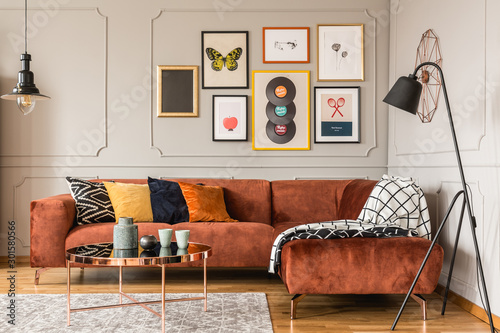 Stampa su Tela Gallery of trendy posters in elegant grey living room interior with brown corner